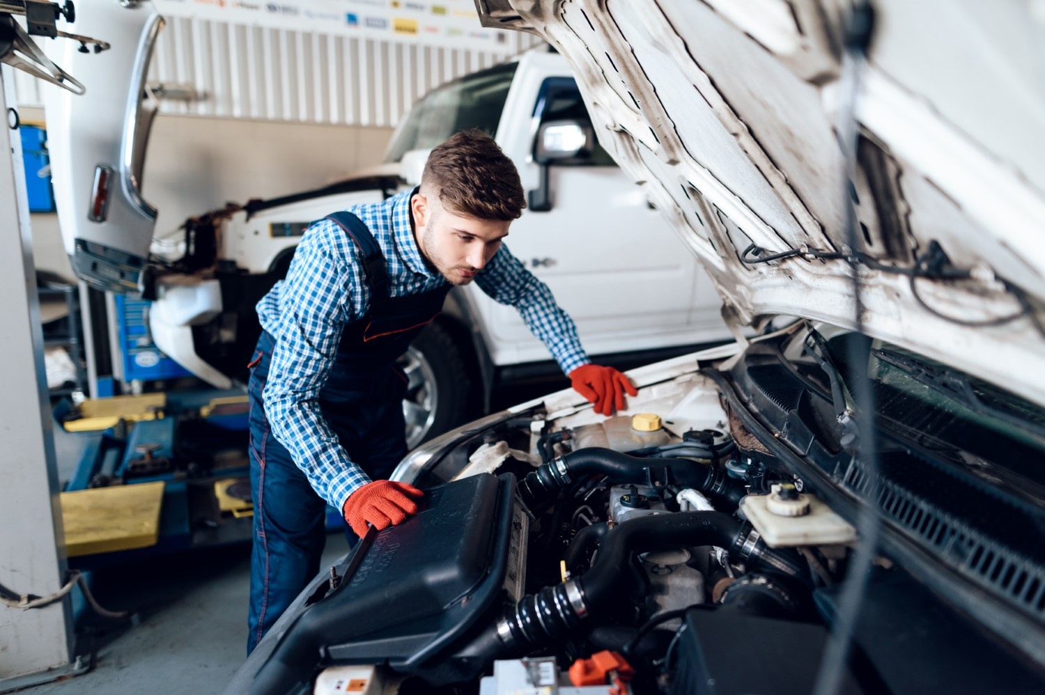 stock-photo-a-young-man-works-at-a-service-station-the-mechanic-is-engaged-in-repairing-the-car-young-767208661-min