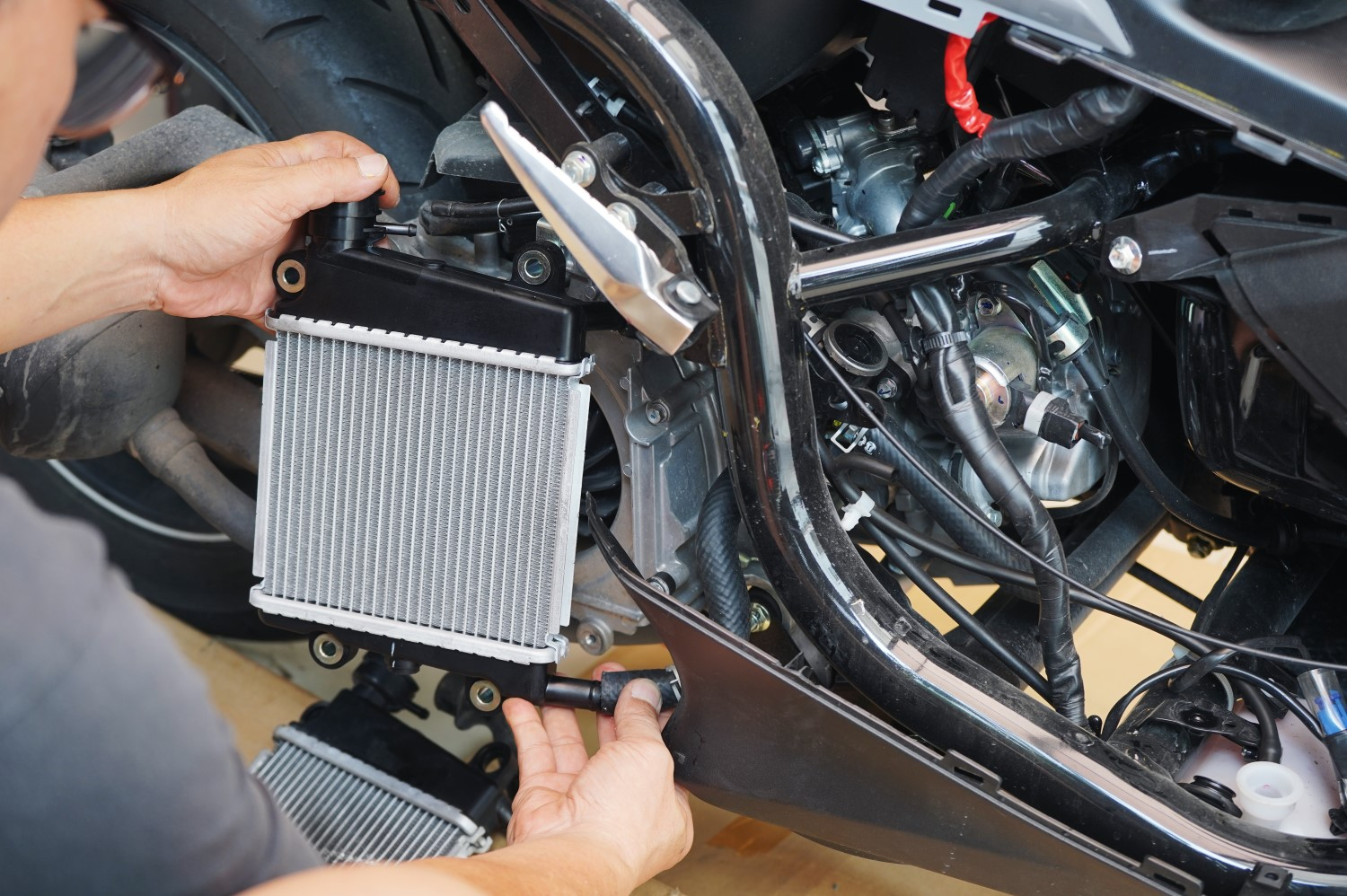 stock-photo-expert-technician-install-radiator-to-motorcycle-or-scooter-radiator-is-main-component-of-the-1472536601